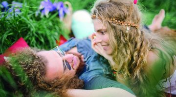 Young beautiful hippie couple lying on grass having fun with dog