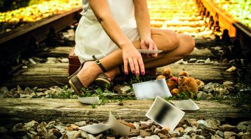 Girl on a railway line stretches out his hand and collects old photographs