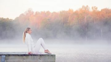 Woman wearing white clothes relaxing and practicing yoga in the mist on the lake footbridge early morning. The morning sun shines on the tree ends.